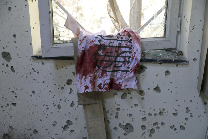 FILE - In this Nov. 3, 2020 file photo, a blood-stained Taliban flag is seen on a window inside the Kabul University after a deadly attack, in Kabul, Afghanistan. In a report released Monday, Feb. 1, 2021, the Special Inspector General for Afghanistan Reconstruction, known as SIGAR, that monitors the billions of dollars the U.S. spends in Afghanistan, said that Taliban attacks in the Afghan capital Kabul are on the rise, with increasing targeted killings of government officials, civil-society leaders and journalists. (AP Photo/Rahmat Gul, File)