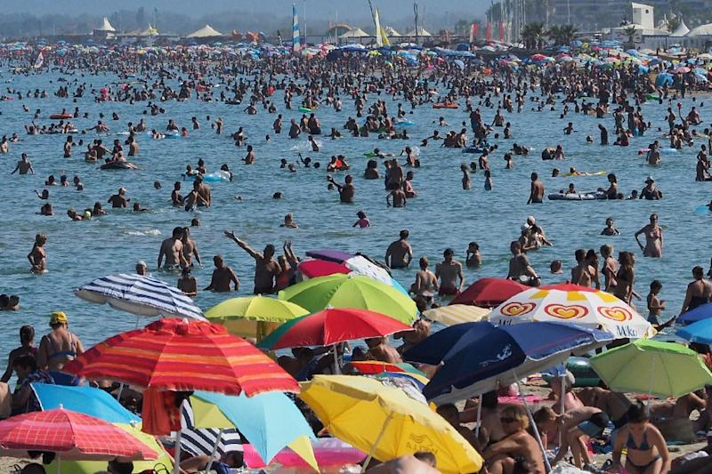 Holidaymakers enjoy the beach in Canet-en-Roussillon, France on August 4, 2017 during a heat wave (AFP Photo/RAYMOND ROIG)