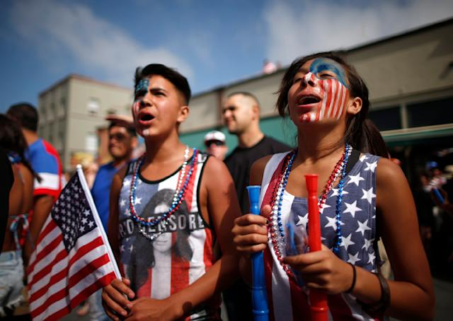 Michelle Lopez, 14, (R) and her brother Erick Lopez, 12, watch the 2014 Brazil World Cup Group G soccer match between Ghana and the U.S. at a viewing party in Hermosa Beach, California June 16, 2014. REUTERS/Lucy Nicholson (UNITED STATES - Tags: SOCCER SPORT WORLD CUP)
