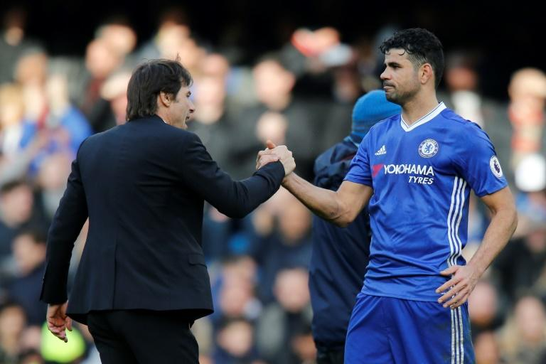 Chelsea's head coach Antonio Conte (L) embraces Chelsea's striker Diego Costa (R) during the English Premier League football match against Arsenal February 4, 2017
