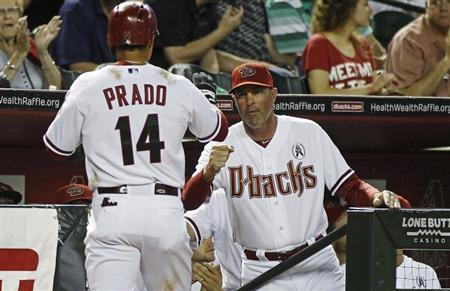 Arizona Diamondbacks' Martin Prado (L) is congratulated by manager Kirk Gibson after scoring against the St. Louis Cardinals during the fifth inning of their MLB National League baseball game in Phoenix, Arizona April 1, 2013. REUTERS/Ralph D. Freso