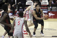 San Diego State's Matt Mitchell (11) drives past UNLV's Caleb Grill (3) during the second half of an NCAA college basketball game Wednesday, March 3, 2021, in Las Vegas. (AP Photo/Joe Buglewicz)