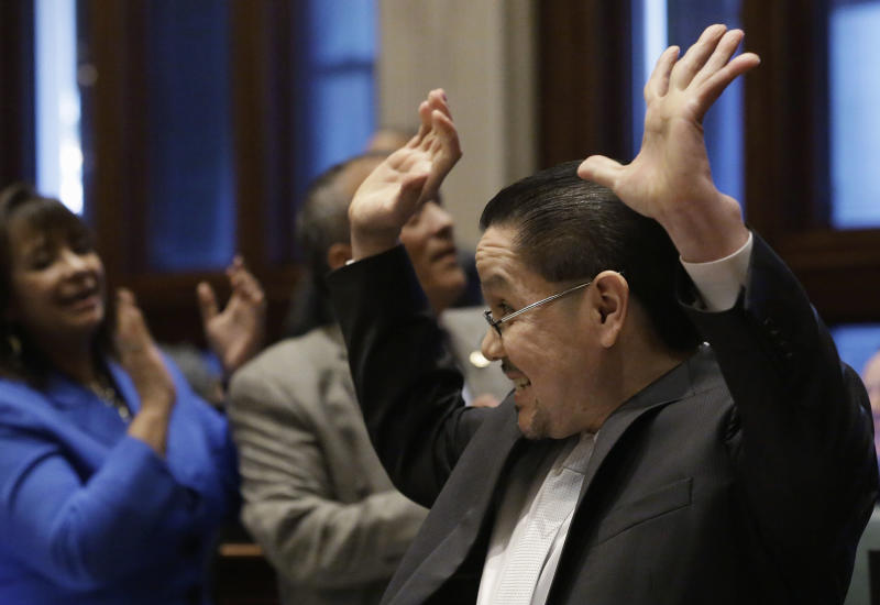 FILE - In this Jan. 8, 2013 file photo, Illinois state Rep. Edward J. Acevedo, D-Chicago, celebrates as the House passes legislation allowing illegal immigrants to obtain driver's licenses during session at the Illinois State Capitol in Springfield. Gov. Pat Quinn is expected to sign the legislation on Sunday, Jan. 27. as Illinois becomes the fourth and most populous state to issue driver's licenses to illegal immigrants, the initiative is still nagged by concerns it has enough safeguards to avoid the identity fraud and other pitfalls faced by the three other states with similar laws. (AP Photo/Seth Perlman, File)