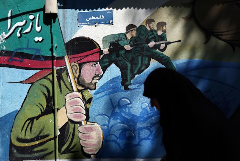 A woman walks past murals of Iranian soldiers marching during the Iran-Iraq war (1980-88), on Palestine square in Tehran (AFP Photo/Behrouz Mehri)