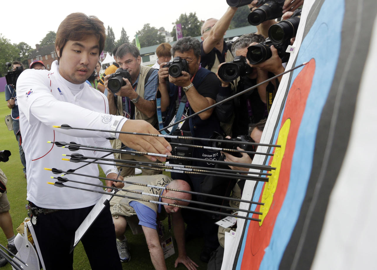 South Korea's Im Dong-hyun collects his arrows during an individual ranking round at the 2012 Summer Olympics, Friday, July 27, 2012, in London. Dong-hyun set a world record in the round with a 699 score.(AP Photo/Marcio Jose Sanchez)