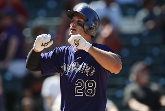 Colorado Rockies' Nolan Arenado celebrates his three-run home run as he crosses home plate against the San Francisco Giants in the fifth inning of the Rockies' 9-2 victory in a baseball game in Denver on Wednesday, Sept. 3, 2014. (AP Photo/David Zalubowski)