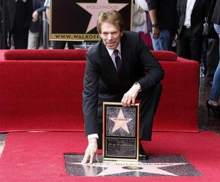 Film and television producer Jerry Bruckheimer poses with his star on the Hollywood Walk of Fame in Hollywood