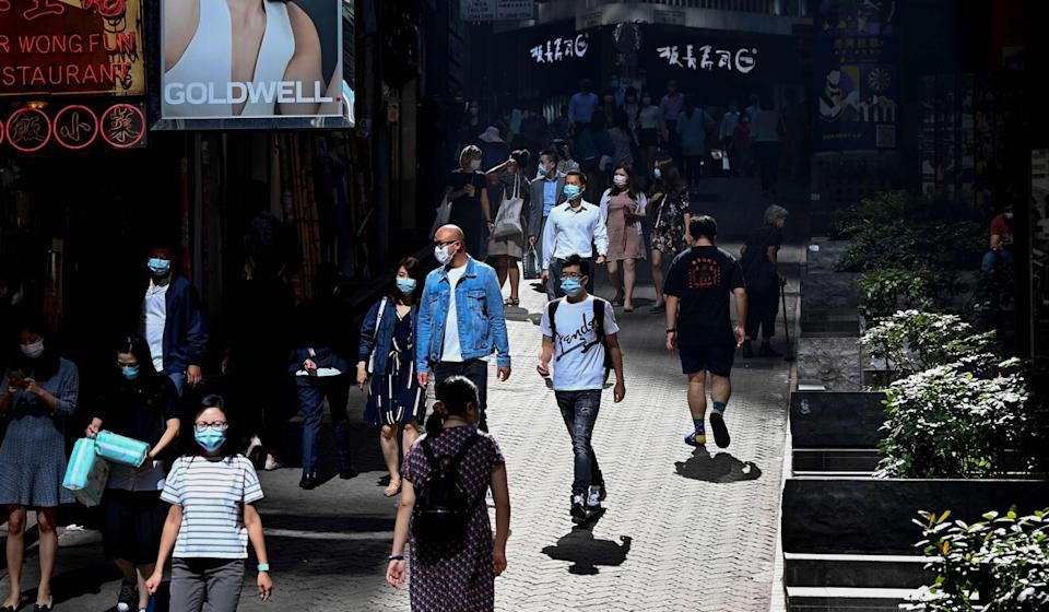 People walk down a street in the Central district of Hong Kong on Tuesday. Photo: AFP