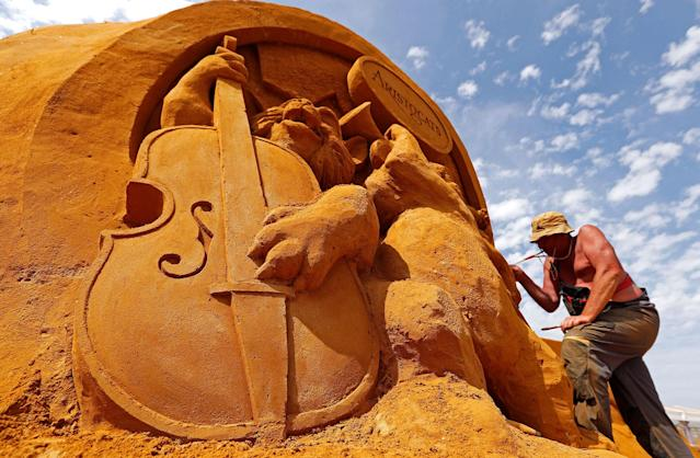 "<p>Sand carver Sergey Aseer from Russia works on a sculpture during the Sand Sculpture Festival ""Disney Sand Magic"" in Ostend, Belgium June 22, 2017. (Yves Herman/Reuters) </p>"