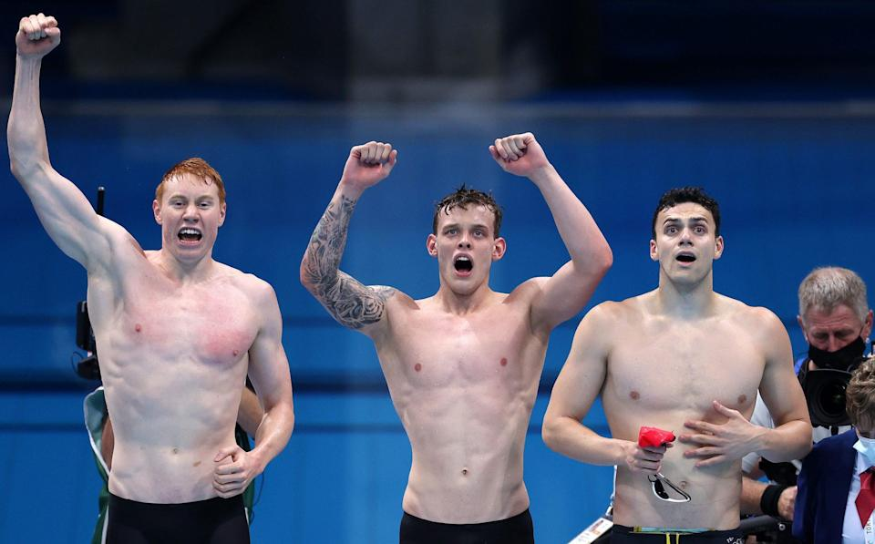 Tom Dean, James Guy and Matthew Richards of Team Great Britain react as teammate Duncan Scott (not pictured) swims the anchor leg during the Men's 4 x 200m Freestyle Relay Final on day five of the Tokyo 2020 Olympic Games at Tokyo Aquatics Centre on July 28, 2021 in Tokyo, Japan. - GETTY IMAGES