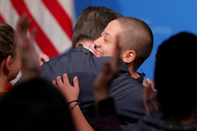 """Emma Gonzalez, a survivor of the February mass shooting at the Marjory Stoneman Douglas High School, is embraced while being welcomed to discuss the """"#NeverAgain"""" push to end school shootings at Harvard University's Kennedy School of Government in Cambridge, Massachusetts, U.S., March 20, 2018. REUTERS/Brian Snyder TPX IMAGES OF THE DAY"""