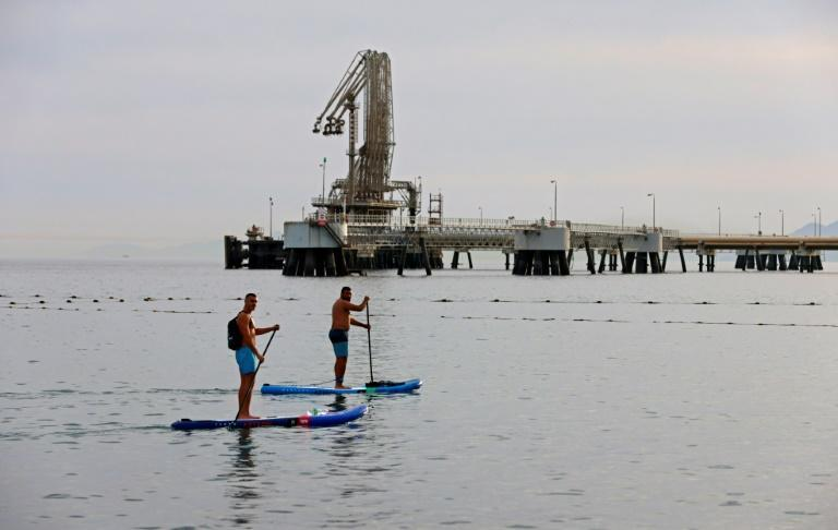 Men row on standup paddle boards in the Red Sea waters near the Eilat-Ashkelon Pipeline Company's (EAPC) oil terminal