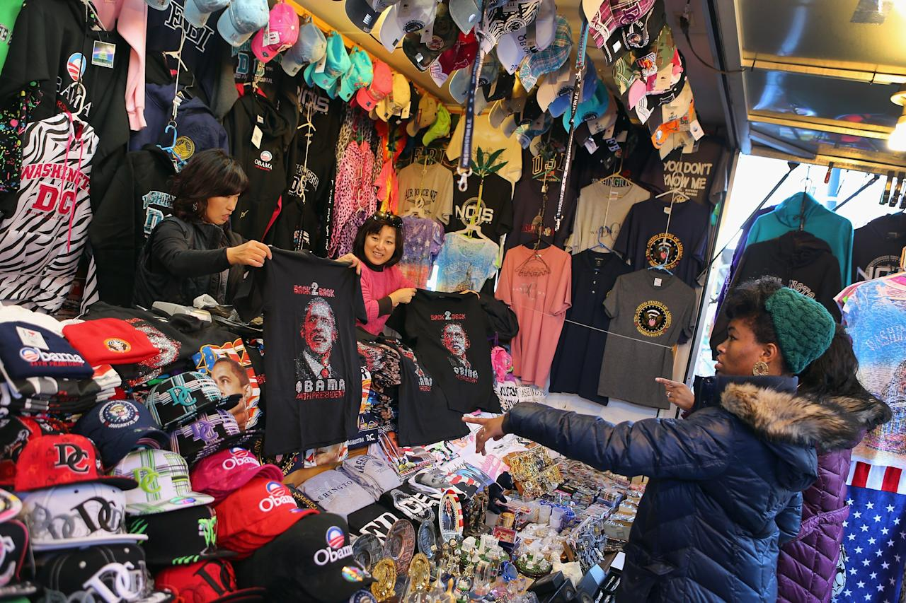 WASHINGTON, DC - JANUARY 20:  souvenir vendor holds a tee-shirt as preparations continue for the Presidential Inauguration on January 20, 2013 in Washington, DC.  The U.S. capital is preparing for the second inauguration of U.S. President Barack Obama, which will take place on January 21.  (Photo by Joe Raedle/Getty Images)