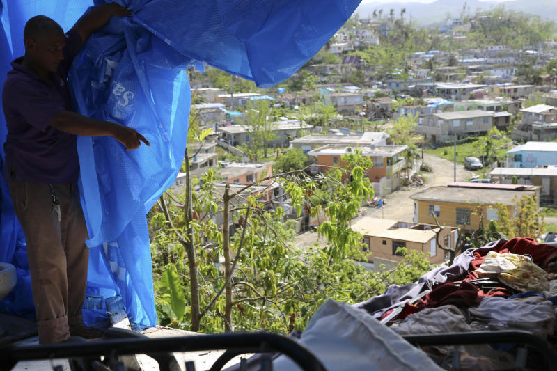 Danny Guerrero Herrera in mid-October shows HuffPost what's behind the blue tarp a charitable organization gave him after Hurricane Maria's winds ripped away most of his home's roof and several walls in Canóvanas, Puerto Rico. (Carolina Moreno/HuffPost)