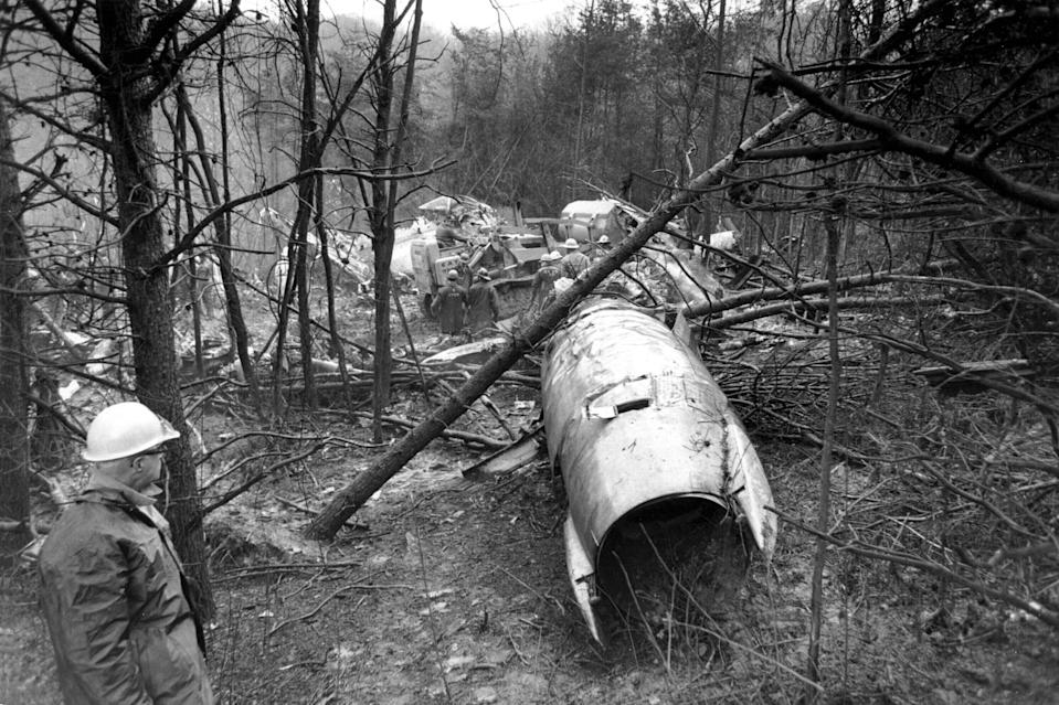 FILE - In this Nov. 15, 1970, file photo, a fireman looks over the wreckage of a plane in Kenova near Huntington, W.Va. Marshall will mark the 50th anniversary of the plane crash that killed all 75 aboard on Saturday, Nov. 14, 2020, on the campus in Huntington. (AP Photo/Henry Griffin, File)