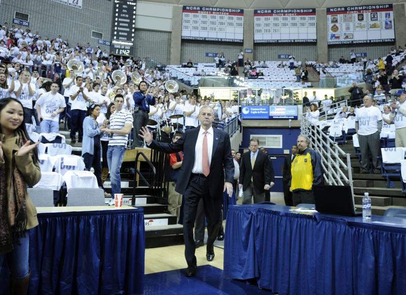 Connecticut coach Jim Calhoun acknowledges the crowd as he enters before his team's basketball game with Pittsburgh  in Storrs, Conn., on Saturday, March 3, 2012. Calhoun missed the Huskies last eight games and had back surgery last Monday. (AP Photo/Fred Beckham)