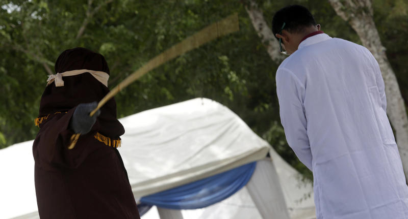 An man is caned in public for having sex outside of marriage in Banda Aceh.