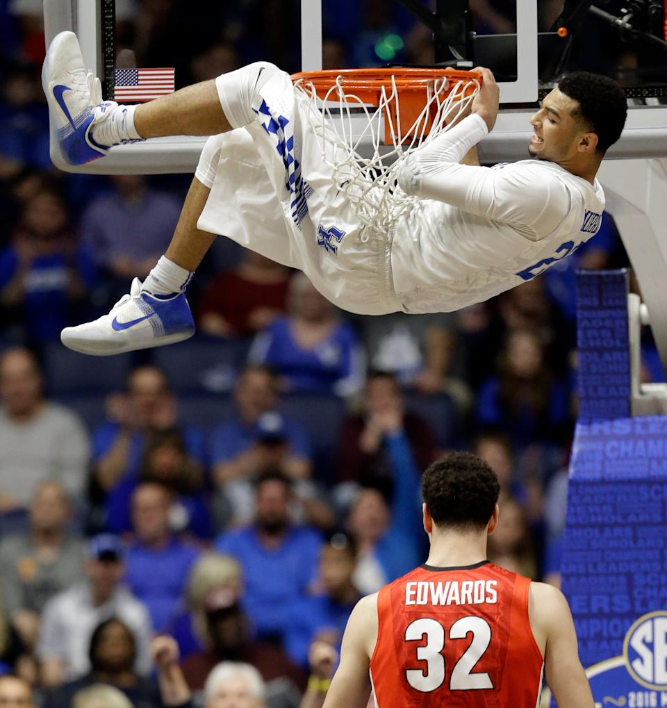 Kentucky's Jamal Murray, top, hangs from the basket after a dunk over Georgia's Mike Edwards, bottom, during the first half of an NCAA college basketball game in the Southeastern Conference tournament in Nashville, Tenn., Saturday, March 12, 2016.