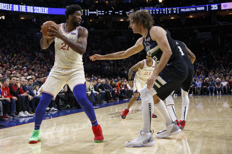 Philadelphia 76ers' Joel Embiid, left, looks to make his move on Milwaukee Bucks' Robin Lopez, right, during the first half of an NBA basketball game, Wednesday, Dec. 25, 2019, in Philadelphia. (AP Photo/Chris Szagola)