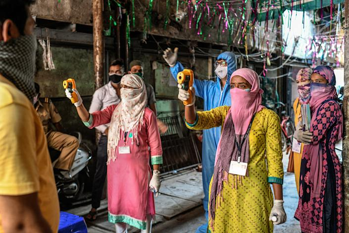 "Health workers check residents' temperatures during a mass screening for COVID-19 symptoms in Dharavi in April. <span class=""copyright"">Atul Loke—Panos Pictures/Redux</span>"