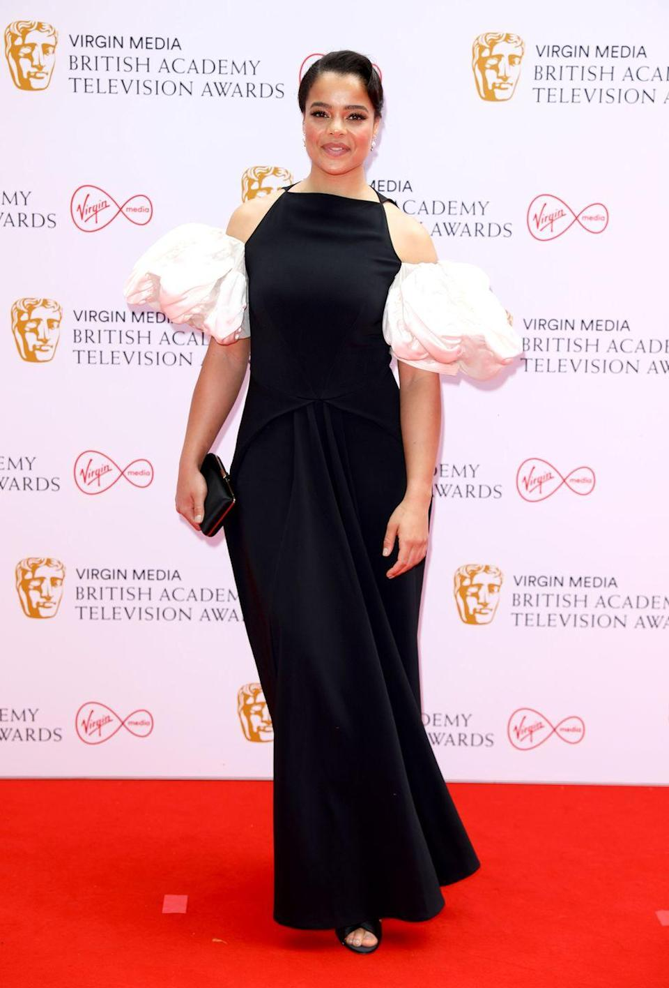 <p>It's A Sin's Lydia West looked chic in a black Loewe gown, which featured white ruffled shoulders.</p>