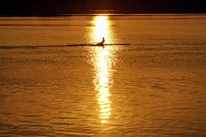 An early morning rower glides through the glare of the rising sun on the Potomac River at the start of a hot day in Washington, Saturday July 20, 2019. Temperatures in the Nation's Capital are expected to reach the upper 90s. (AP Photo/J.David Ake)