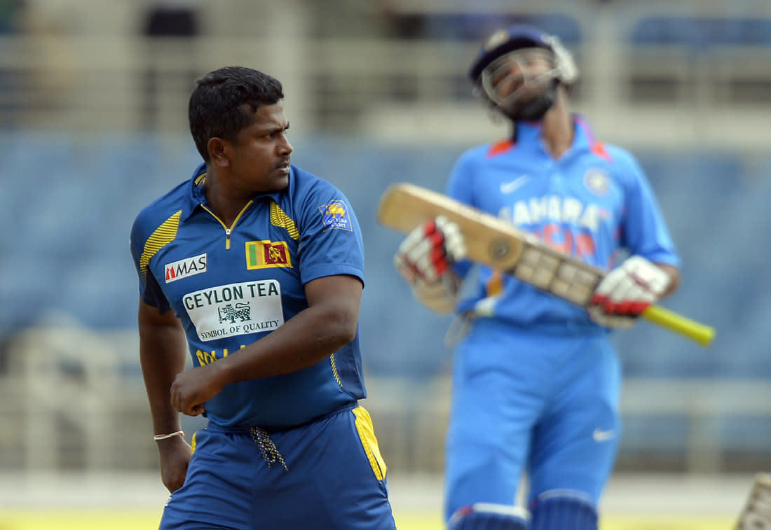 Sri Lankan cricket Rangana Herath celebrates dismissing Indian bastman Shikhar Dhawan (back) during the third match of the Tri-Nation series between India and Sri Lanka at the Sabina Park stadium in Kingston on July 2, 2013. Sri Lanka have scored 348/1 at the end of their innings. AFP PHOTO/Jewel Samad