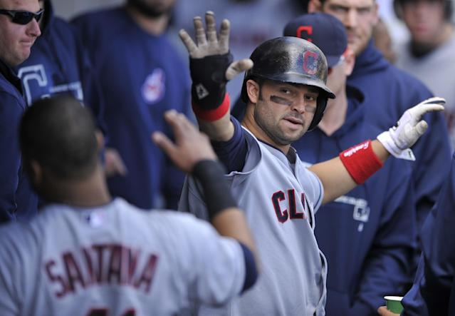 Cleveland Indians' Nick Swisher celebrates with teammates in the dugout after scoring on a double by Ryan Raburn during the fifth inning of a baseball game against the Chicago White Sox in Chicago, Friday, Sept. 13, 2013. (AP Photo/Paul Beaty)