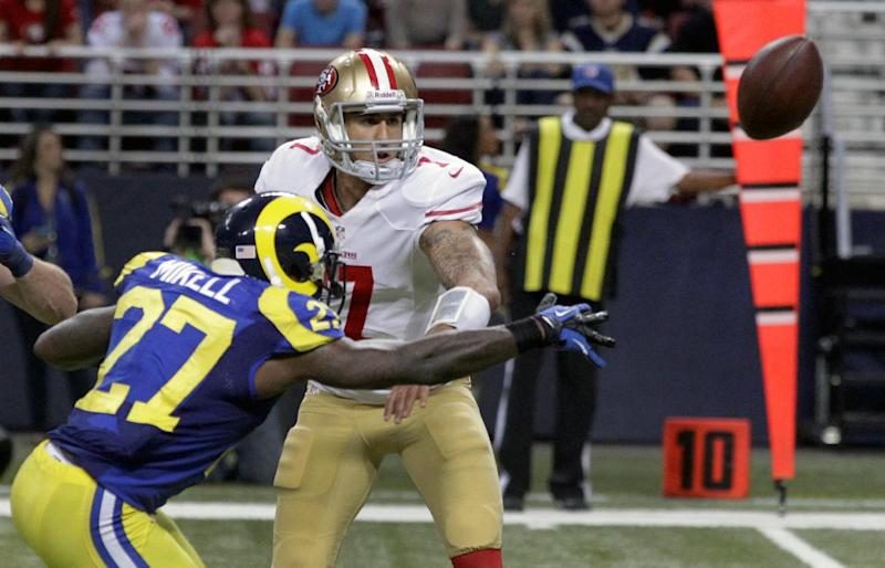 San Francisco 49ers quarterback Colin Kaepernick, right, tries to toss the ball to teammate Ted Ginn as St. Louis Rams' Quintin Mikell (27) defends during the second half of an NFL football game on Sunday, Dec. 2, 2012, in St. Louis. The play was ruled a fumble, recovered by Rams' Janoris Jenkins who took it in for a touchdown. (AP Photo/Seth Perlman)