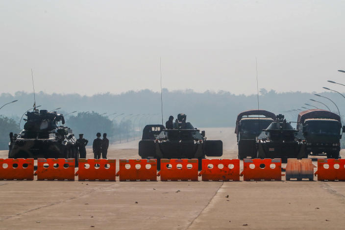 Myanmar's military stand guard at a checkpoint manned with an armored vehicles blocking a road leading to the parliament building, February 2, 2021, in Naypyitaw, Myanmar. / Credit: AP
