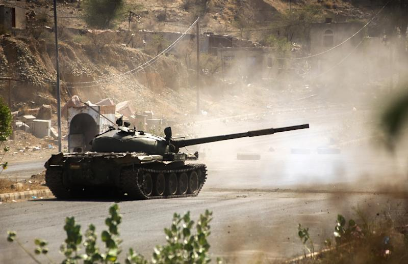 A fighter loyal to Yemen's exiled President Abedrabbo Mansour Hadi fires from a tank during clashes with Shiite Huthi rebels west of the city of Taez on March 21, 2016 (AFP Photo/Ahmad Al- Basha)