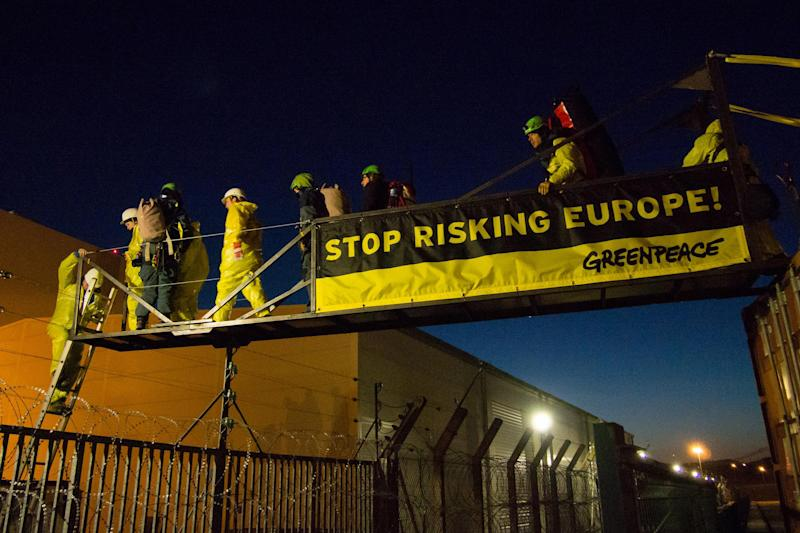 """In this photo provided by environmental group Greenpeace, activisits hang a banner reading """"Stop Risking Europe"""" next to one of the reactors at the Fessenheim nuclear power plant, eastern France, Tuesday, March 18, 2014. More than 60 Greenpeace activists have occupied a nuclear plant in eastern France to protest the nation's reliance on atomic power. In a statement Greenpeace France said the activists had come from 14 countries across Europe """"to denounce the risk to Europe from France's nuclear power,"""" and to promote a transition to other energy sources. (AP Photo/Greenpeace, Bente Stachowske)"""
