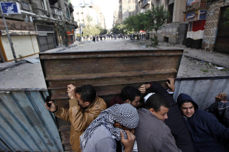 Protesters  take a cover during clashes with Egyptian riot police near the interior ministry in downtown cairo, Egypt, Sunday, Nov. 20, 2011. Firing tear gas and rubber bullets, Egyptian riot police on Sunday clashed for a second day with thousands of rock-throwing protesters demanding that the ruling military quickly announce a date to hand over power to an elected government. (AP Photo/Khalil Hamra)