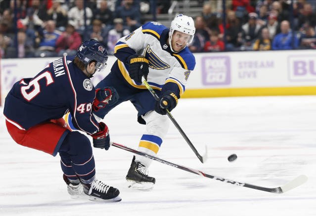 St. Louis Blues' Carl Gunnarsson, right, of Sweden, passes the puck across the blue line as Columbus Blue Jackets' Vladislav Gavrikov, of Russia, defends during the first period of an NHL hockey game Friday, Nov. 15, 2019, in Columbus, Ohio. (AP Photo/Jay LaPrete)
