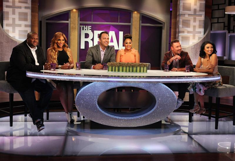 """This undated publicity photo released by Warner Bros. shows hosts Tamar Braxton, second left, with husband, Vincent Herbert, left, Tamera Mowry-Housley, center, with husband, Adam Housley, and Jeannie Mai, right, with husband Freddy Harteis, on the set of """"The Real."""" The ladies of """"The Real"""" discussed changing their last names after getting married and Braxton revealed she'll soon be known as Tamar Herbert during an episode, """"Bring Your Husband To Work Day."""" """"The Real"""" is taking a different approach to the TV talk show format with a younger, multi-ethnic panel. (AP Photo/Warner Bros., Michael Rozman)"""
