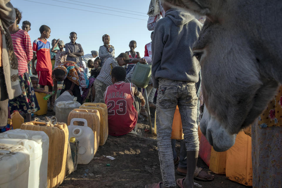 A Tigray refugee, who fled the conflict in the Ethiopia's Tigray and wearing a Michael Jordan jersey, fills his water jug at Hamdeyat Transition Center near the Sudan-Ethiopia border, eastern Sudan, Thursday, Dec. 3, 2020. Ethiopian forces on Thursday blocked people from the country's embattled Tigray region from crossing into Sudan at the busiest crossing point for refugees, Sudanese forces said.(AP Photo/Nariman El-Mofty)