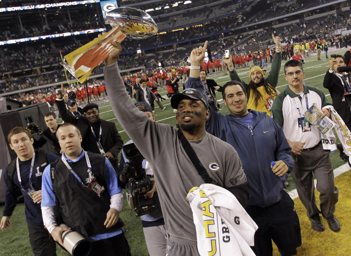 FILE - In this Sunday, Feb. 6, 2011, file photo, Green Bay Packers' Charles Woodson holds the Vince Lombardi Trophy after NFL football Super Bowl XLV in Arlington, Texas. Woodson was one of the best football players of all time, joining Hall of Fame running back Marcus Allen as the only players to win a Heisman Trophy, AP Rookie of the Year, AP Player of the Year and a Super Bowl. (AP Photo/Dave Martin, File)