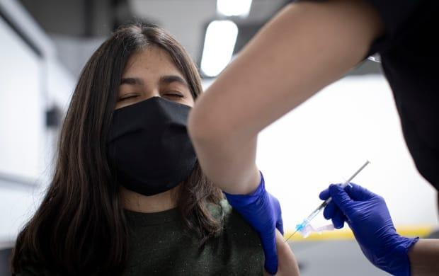 Black Creek Community Health volunteer Jasleen Kambo, 18, gets her first dose of the Moderna COVID-19 vaccine at a clinic run by Humber River Hospital in Toronto last month. (Evan Mitsui/CBC - image credit)