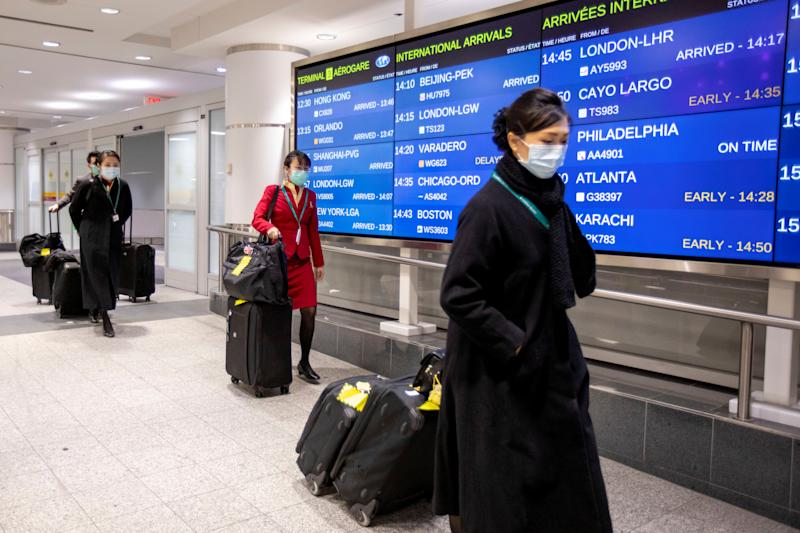 Flight crew members wear masks at Pearson airport arrivals, shortly after Toronto Public Health received notification of Canada's first presumptive confirmed case of coronavirus, in Toronto, Ontario, Canada January 26, 2020. REUTERS/Carlos Osorio