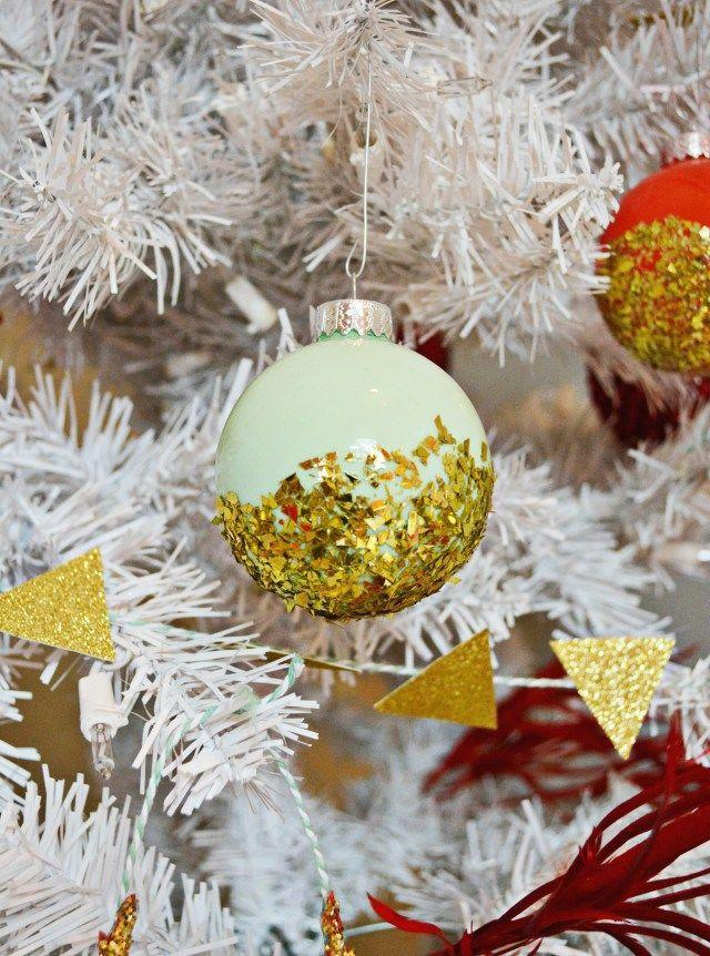 """<p>You can never go wrong with gold glitter on a white faux Christmas tree. </p><p>Get the tutorial at <a href=""""http://www.ajoyfulriot.com/2014/12/03/dipped-glitter-ornaments/"""" rel=""""nofollow noopener"""" target=""""_blank"""" data-ylk=""""slk:A Joyful Riot"""" class=""""link rapid-noclick-resp"""">A Joyful Riot</a>.<br></p>"""