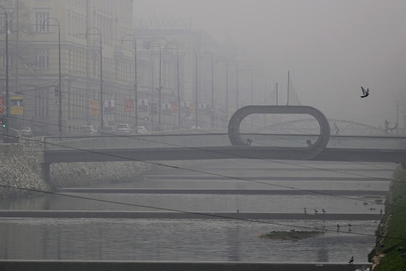 Smog covers Miljacka river in downtown Sarajevo, Sunday, Dec. 8, 2019. The local government in Sarajevo issued a warning to residents to avoid spending time outdoors as extremely high pollution levels are being recorded in the air of Bosnian capital in last two days. (AP Photo/Eldar Emric)