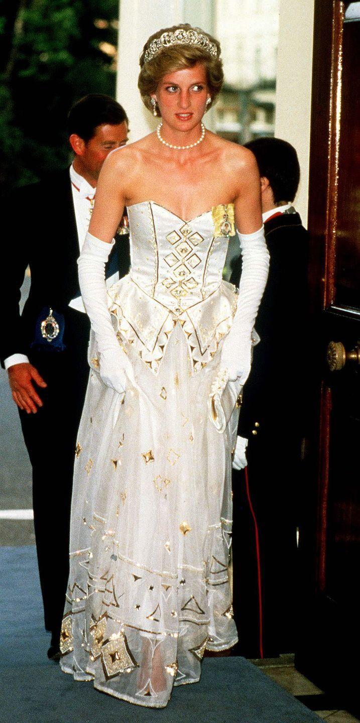 <p>Princess Diana opted for a more traditional look for an event at the German Embassy in London. The princess chose elbow-length gloves, a pearl necklace and earrings, the Spencer tiara, and a Catherine Walker white and gold gown. </p>