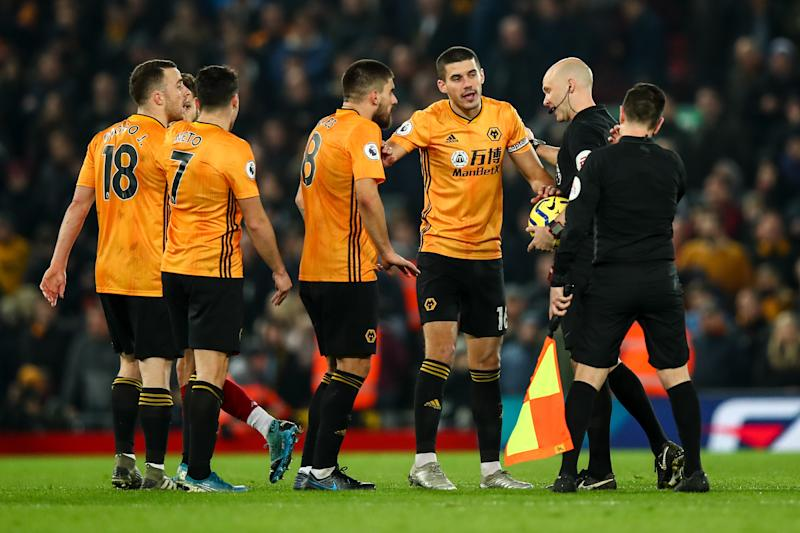 LIVERPOOL, ENGLAND - DECEMBER 29: Players of Wolverhampton Wanderers surround Referee Anthony Taylor at half time after a VAR decision to disallow a goal during the Premier League match between Liverpool FC and Wolverhampton Wanderers at Anfield on December 29, 2019 in Liverpool, United Kingdom. (Photo by Robbie Jay Barratt - AMA/Getty Images)