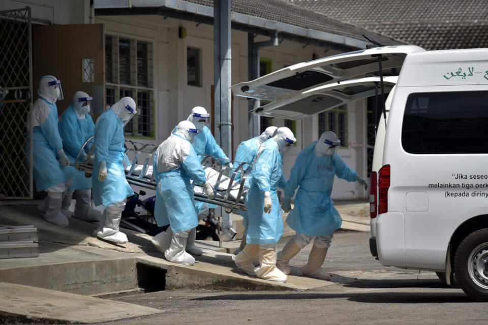 Health personnel transport the remains of a Covid-19 patient for burial at the Labuan Nucleus Hospital June 7, 2021. — Bernama pic