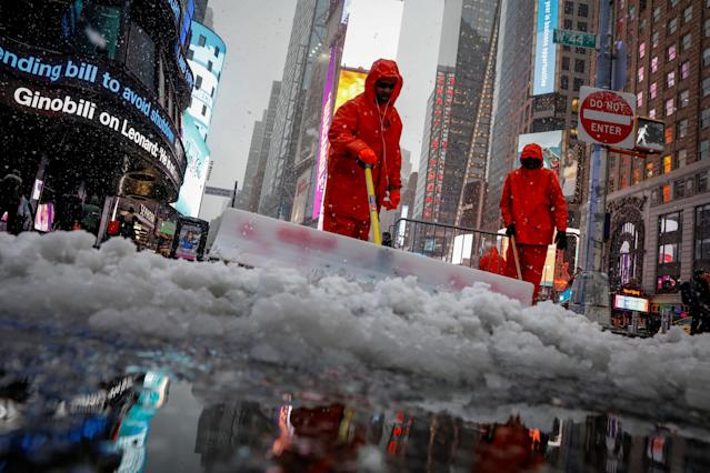 Workers clear snow during a winter nor'easter storm in Times Square in New York City, U.S., March 21, 2018. REUTERS/Brendan McDermid TPX IMAGES OF THE DAY