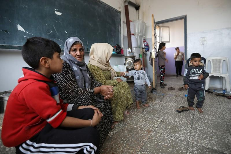 Displaced Kurdish family, who fled violence after a Turkish offensive in northeastern Syria, sit at a public school in Hasakah