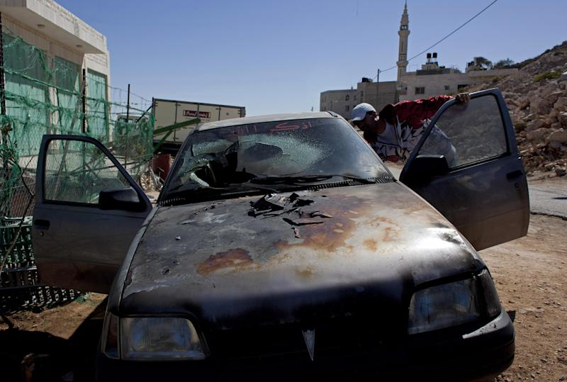 A Palestinian man inspects a burned vehicle in the village of Burka, east of the West Bank city of Ramallah, Thursday, Oct. 10, 2013. Palestinian residents of the village said masked Jewish settlers torched three cars and defaced a mosque during an overnight attack. (AP Photo/Nasser Nasser)