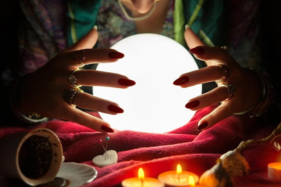 Hands of an female fortune teller around a crystal ball - Credit: Cherries/Adobe Stock