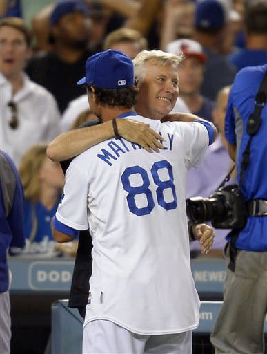Los Angeles Dodgers manager Don Mattingly (88) gets a hug from co-owner Mark Walter after the Dodgers' baseball game against the San Francisco Giants, Wednesday, Oct. 3, 2012, in Los Angeles. The Dodgers won 5-1. (AP Photo/Mark J. Terrill)