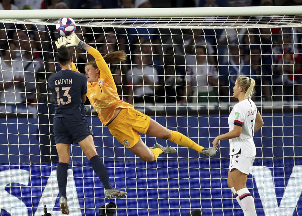 United States goalkeeper Alyssa Naeher (1) deflects the ball away from France's Valerie Gauvin during the Women's World Cup quarterfinal soccer match between France and the United States at the Parc des Princes, in Paris, Friday, June 28, 2019. (AP Photo/Francisco Seco)